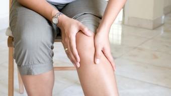 Piernas cansadas. Mujer tocándose la pierna.